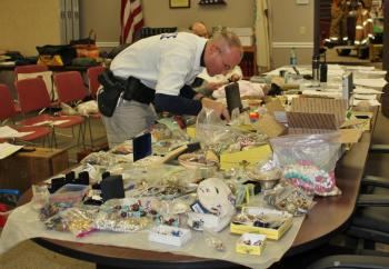 Officer Mercier searches through some of the goods recovered from the Fuller residence at Boothbay Harbor Town Office March 28. Police have thousands of items to sort through and compare to individual itemized lists from area burglaries. SUE MELLO/Boothbay Register