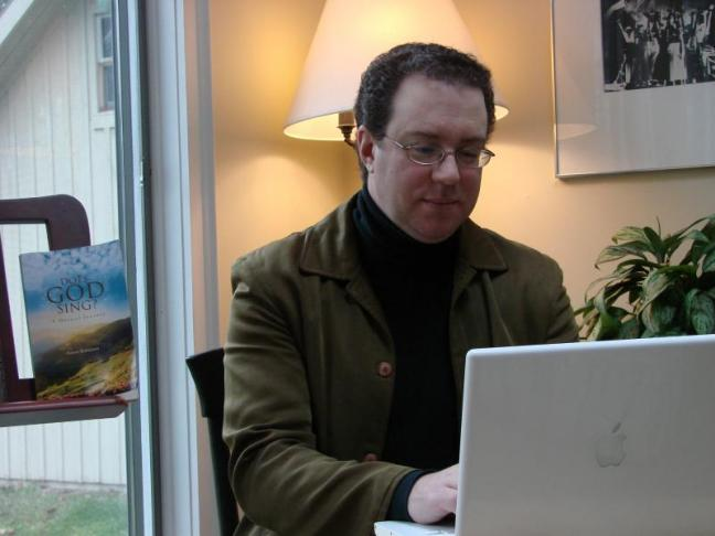 """Maestro turned author Aaron Robinson at home in Alna in front of his new book, """"Does God Sing? A Musical Journey."""" SUSAN JOHNS/Wiscasset Newspaper"""