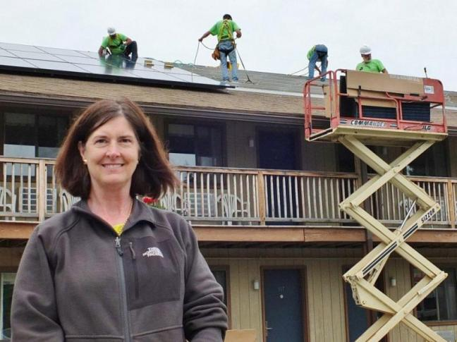 Ann (Robinson) Goggin of Goggin Energy oversees the solar panel installation at Boothbay Harbor's Flagship Inn on June 13. Goggin's solar panels convert direct current from the sun into alternating current right at the solar panel. The panels will offset the Flagship's electricity bill starting July 1.