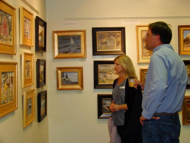 Artists Anne Blair Brown and Richard Oversmith pause over Stuart Roper's works.  LISA KRISTOFF/Boothbay Register