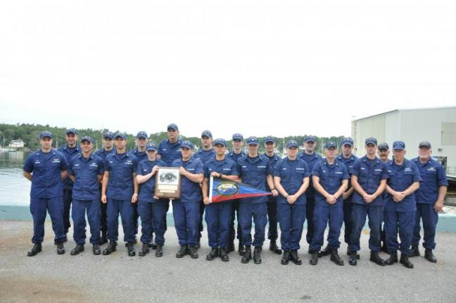 THE COAST Guard Station was recently awarded with the Sumner I. Kimball Award, which is given to the station that keeps exemplary care of boat material equipment, boat and personal protective equipment, has superlative crew proficiency and compliance with training requirements and readiness. Here, the crew stands near the harbor with the plaque and pennant they received. BEN BULKELEY/Boothbay Register