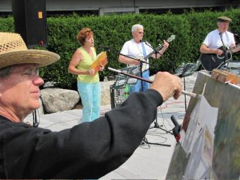 John Seitzer while painting at last year's Art@Waterfront Park while the Greenfields perform onstage. Seitzer, the Greenfields and dozens of artists perform or exhibit on Saturday, Sept. 1 at Whale/Waterfront Park on Commercial Street in Boothbay Harbor.