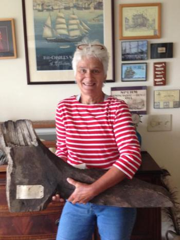 Sally Bullard holds a piece of the 'Charles W. Morgan,' originally removed during the first major restoration work performed between 1967 and 1970. The hanging knee timber is hand hewn oak. Hanging knees were vertical pieces cut from the natural section of oak where a limb grew out of the trunk and were fastened with large drift pins of iron or brass. LISA KRISTOFF/Boothbay Register